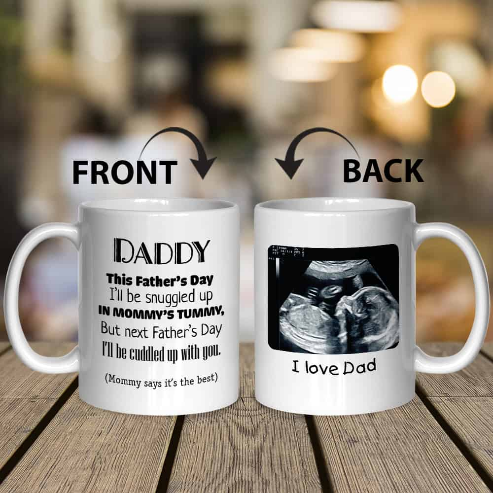 "A mug for dad-to-be with a funny saying: ""Daddy This Father's Day I'll Be Snuggled Up In Mommy's Tummy"""
