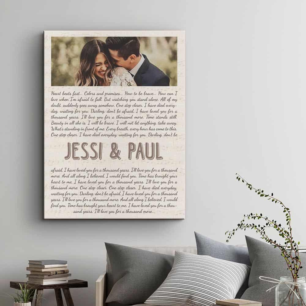 A photo canvas print with custom song lyrics on that is hung above a sofa