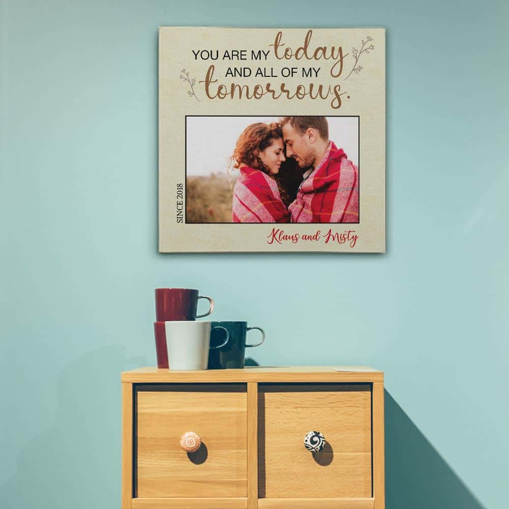 """A custom photo canvas with the quote """"You Are My Today And All Of My Tomorrows"""" hung above a bed"""